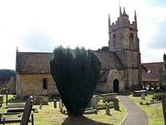 Bathstone building with prominent four stage tower at the right hand end. Partly obscured by a yew tree.