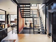 """Moseley notes the home's distinctive staircase as one of her favorite features. """"When the steel was ordered from the steelyard,"""" she says, """"it was marked with our metalworker's name, for easy pickup. That scribble still exists in random places in the staircase and is very industrial—we love it!"""" Hand-welded by Mike Carman, a local contractor, the staircase runs through all three floors, and it was custom-sized to fit the dimensions of the shipping containers, measuring nine-feet-six-inches…"""