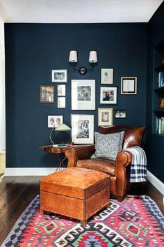 Family living room with dark blue walls, colorful rug and leather armchair | NONAGON.style