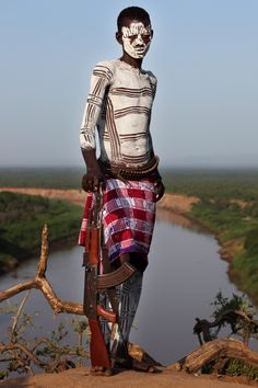 Africa | Young Karo warrior with typical body painting and a Kalashnikov, which nowadays almost every young Karo man is wearing. In the background the Omo river.  Ethiopia | ©Dietmar Temps