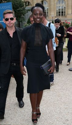 Lupita Nyong'o attended the Martin Margiela Fall 2015 Couture Show in a Martin Margiela Resort 2016 Black Lace Panel Dress + Black Dior 'So Real' Shades