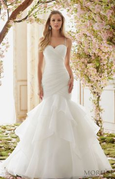 Morilee | Madeline Gardner Style 6833 Bridal Gown. This modern mermaid beauty is accented with delicate crystal beaded straps for just the right amount of bling. The sweetheart neck bodice has ruching along to the layers of organza ruffles on this glam wedding dress.