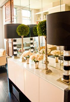 Side table styling with symmetrical lamps, topiaries and silver vases with roses.  And of course the mirror wall.