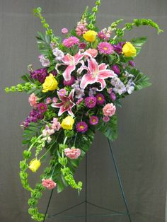 Crescent shaped standing funeral spray. #funeralflowers #stargazers