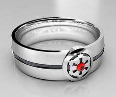 Star Wars tribute Empirial Crest Ring! This ring comes with a Chatham lab created Ruby for a nice accent stone. Also available with lab created emerald, or sapphire upon request. This 6mm wide wedding band is made from recycled silver and is handmade with a comfort fit to your size. The ring is carved from wax, then cast in the metal. From there it is finished by hand to achieve a great wearable look.  Ring Specs: ● 6mm width (7 mm at emblem) ● 1.5mm Thickness- good weight, sturdy…