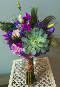 Handtied Bouquet: Large Succulents,  Purple Trick, Lavender hydrangea,  Purple Lissianthus,  Celosia, Brunia accented with Peacock Feathers.  Designed by Scarlett's Flowers