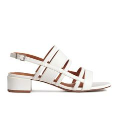 Sandals in imitation leather with grained details. Adjustable ankle strap with metal buckle, imitation leather lining and insoles, and rubber soles. Heel height 1 1/2 in.