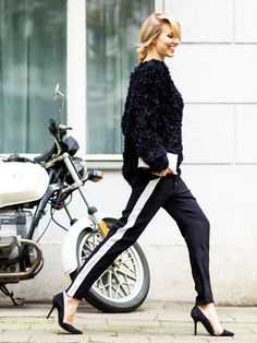 Black textured sweater, black pants with white side-stripe, black pumps, and white clutch