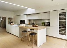 Kitchen Architecture's bulthaup b3 furniture in kaolin laminate with stainless steel and Carrara marble work surfaces and a solid oak bar.