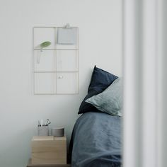 Calm bedroom with blue linen sheets in a modern Scandinavian city home in Stockholm, Sweden. Grid by Wallment Design, made in Finland.