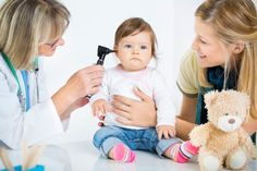 Doctor examining toddler's ear with mom smiling