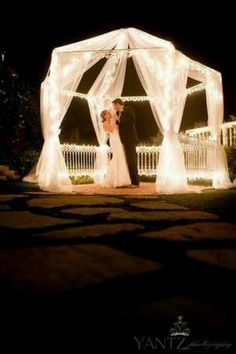 Tulle and string lights frame this beautiful wedding couple's picture. Use LED string light sets so you can connect several end-to-end and not worry about the heat of the lights. Shop online at http://www.partylights.com/LED/LED-String-Lights. #lights #wedding