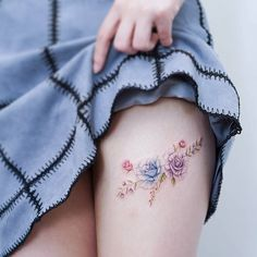 Blue and purple rose tattoo on the left thigh.