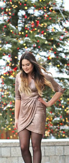 The most flattering wrap dress under $70! | Fashion and beauty blogger Mash Elle shares a holiday metallic wrap dress for less! This dress is paired with Marc Fisher ankle booties, a Baublebar Choker Necklace and tights!