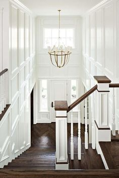 This chic two story foyer features walls clad in decorative trim moldings illuminated by a brass Lancaster Chandelier.