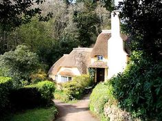 """The fairytale cottage that follows is located in Selworthy, a small village in Somerset, England.  It features a picturesque """"stepped"""" or """"tiered"""" roof line covered  with  thatch, and light stucco walls.      An oversized front-facing chimney adds to the charm of this exquisite architectural jewel!"""