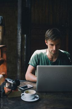 Young designer working on laptop at his home office by Marija Savic #stocksy #realstock
