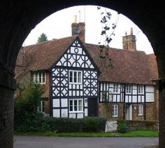 Goose Green, Gomshall, England, seen through the railway arch are the Old Malthouse Cottages. These are a pleasing mix of Tudor style, stone, brick and half-timbering.