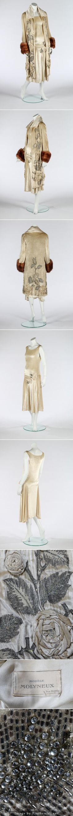 Edward Molyneux couture evening ensemble, circa 1928-29. printed silk label 'Molyneux, 3 Rue Royale', and indistinctly numbered 32553, of sumptuous ivory velvet, the dress with drapes to the dropped waistline, trimmed with large velvet roses inset with pearls and rhinestones with bugle beaded, pearl and rhinestone leaves. The matching coat also covered with lavishly embroidered and beaded roses front and back, plain satin collar, lined in ivory satin. KTA