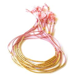 TenThings. GOLD Beaded. Silk Tassel. Friendship Bracelet.A grown up version of version the always in style Friendship Bracelet. Understated, feminine silk bracelets. 40 gilded beads lay ever so delicately on the wrist. Adjustable sliding closure.Handmade in 14k gold filled GOLD beads with your choice silk cord. These look beautiful stacked with other friendship bracelets or bangles. If you'd like to order several in different colors and metals, please specify in notes to...