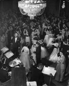 Nina Leen / Via Time Inc.  Young couples at a formal dance dreamily sway on the crowded floor of dim, chandelier-lit ballroom.