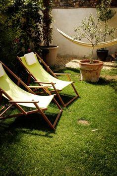 芝のある庭に、布が黄緑の木製デッキチェアを2つ置き、ハンモックをつるします。植木や大き目の鉢植えのそばで、芝生の上のチェアに座りひなたぼっこができます。