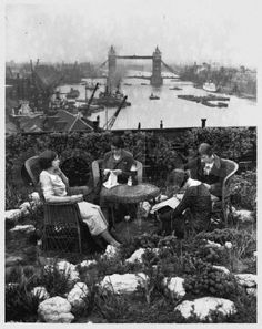 London, England, UK --- A group of young city workers enjoy a lunchtime break in a roof garden overlooking Tower Bridge, on the River Thames. --- Image by ? Hulton-Deutsch Collection/CORBIS