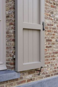 Putty colored shutters with overgrouted brick/ At least these shutters look like they could cover the window. Proper.