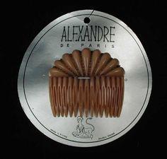 """Sierkam, insteekkam van leverkleurig kunststof met koperkleurige schakelkettinkjes, vastgezet op de originele verpakkingskaart, """"Alexandre de Paris"""" - zijkammetje"""