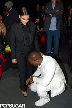 Kanye West helped Kim Kardashian with her shoe at Paris Fashion Week.