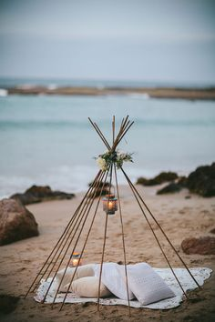 Beach wedding teepee with lanterns and pillow cushions