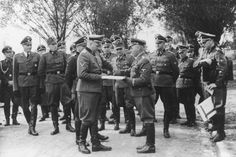 "Nazi officers watch as Commandant Richard Baer exchanges documents with Karl Bischoff during the dedication of the new SS hospital in Auschwitz.  The original caption reads ""Besichtigung"" (tour).  Dr. Eduard Wirths stands on the far left.  Dr. Heinz Baumkoetter is fifth from the left.  In the center are Commandant Richard Baer, Karl Hoecker and Rudolf Hoess and Karl Moeckel.  Holding the documents on the right is (most probably Werner Jothann). To the right of Wirths, is (probably August…"