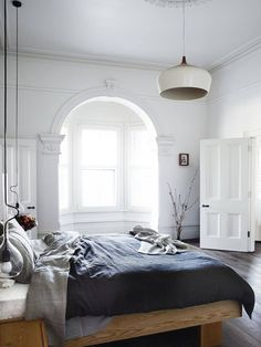 Cozy and snuggly bedroom with crisp, grayscale colors, modern light fixture and branches for décor