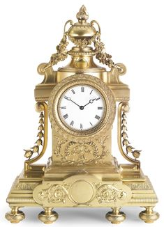 A Fabergé silver-gilt mantle clock, Moscow, circa 1900, in Louis XVI style, on a rectangular partly fluted base with central frontispiece mounted with scrolling foliage, the circular dial with reeded and chased wave design border surrounding a white enamel dial with Roman numerals, with foliate swags to both sides, torch final, on six ribbon-tied reeded bun feet.