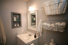 I love this idea for storage of towels - baskets over the toilet.
