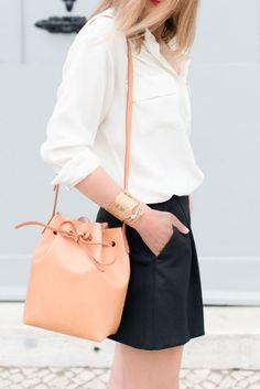 Une chemise souple blanche, une petite jupe noire et un sac seau de couleur claire. Tout en simplicité !