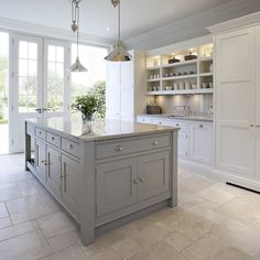 This bright and light shaker style kitchen is painted in bespoke Tom Howley paint colour; Chicory, the light granite worktops and marble flooring create a heightened sense of space.