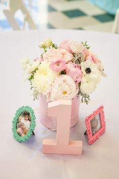 Flowers, photographs in tiny frames, and a big number one make a fitting 1st birthday centerpiece.  See more first girl birthday party ideas at www.one-stop-party-ideas.com