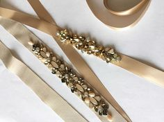 Add a touch of sparkle to your bridal gown! Delicate Champagne Gold Skinny Satin Vintage Inspired Crystal Jewel Embellished Ribbon Bridesmaids Sash features a tonal mix of champagne, beige and gold crystals. Champagne Satin sash is 5/8 wide and 80 long with a tie back closure.