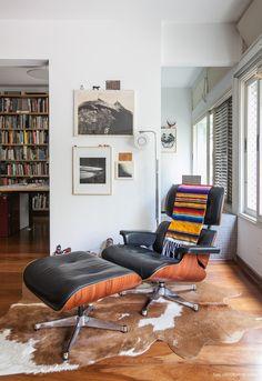 Cantinho de leitura com poltrona Eames, tapete feito com pele de vaca e objetos de artesanato.