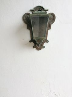 "Detail of one of the many light fixtures in bronze. There are different models throughout the palace, and they all seem to be from the mid 20th c., when extensive restoration was done. The lanterns and sconces are therefore relatively new, but beautiful and appropriate. This is a great example, with bold ""ears"" at the wall plate and inverted-heart vents at the top."