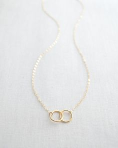 Double Circle Necklace in gold by Olive Yew. Two tiny interlocking gold circles create a simple look that resembles little wedding bands. Interlocking Circle Necklace, Gold Circle Necklace, Simple Necklace, Simple Jewelry, Cute Jewelry, Gold Jewelry, Jewelery, Jewelry Accessories, Pendant Necklace