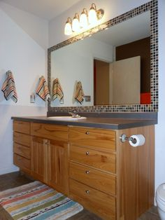 DIY tiled, framed bathroom mirror. But I would use a different color tile and darker cabinets
