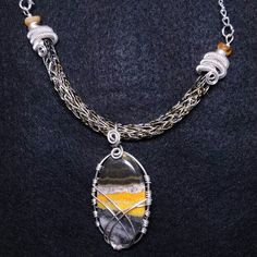 4 tone hematite, gold, black,  and silver non-tarnish viking knit necklace with silver spiral end caps, citrine beads and a silver caged Bumblebee Jasper pendant.