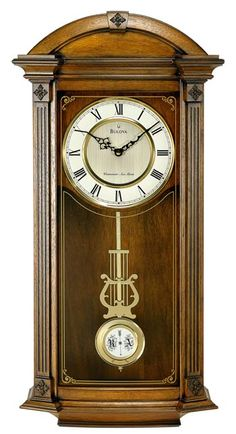 "Old World walnut finish in a solid wood case with angled corners with fluted pilasters and decorative carved accents. Two-tone metal dial behind a decorative screened curved glass lens. Triple-chime movement plays choice of Westminster, Ave Maria or Bim-Bam melody on the quarter hour with hour count. Volume control and Night time shut-off. Size: H: 29.75"" W: 14"" D: 5.5"""