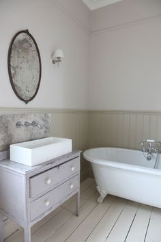Dresser turned into a bathroom vanity with a modern sink. Claw foot tub and wainscoting
