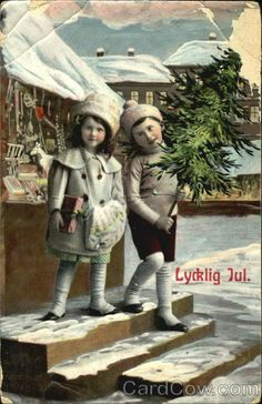 Two girls in the snow with present and Christmas Tree