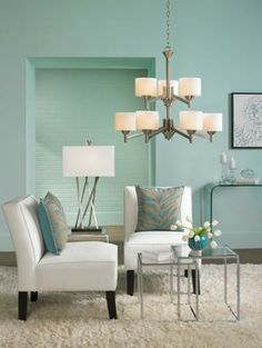Calming and contemporary, this aqua living room design feels fresh.  Soft aqua and crisp white freshen up a contemporary living room! This color combo is classic and chic, and really pops when paired with chrome accents. Add interest to plain walls and furniture with a little pattern - subtle aqua and beige zebra-print pillows add understated texture on the matching slipper chairs, while a piece of contemporary floral art breaks up a large expanse of wall.