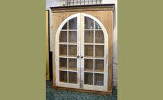 Custom cabinet made with salvaged arched windows