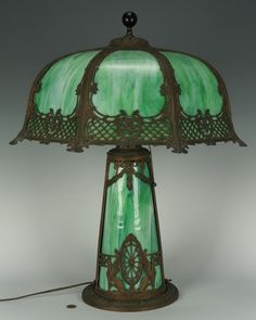 """Large slag glass table lamp. Green slag glass shade, base with metal overlay decoration featuring swags and griffins. 23 3/4"""" H x 20"""" W. American, early 20th century."""